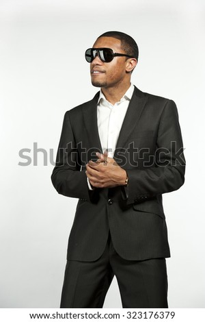 A young vogue style black male wearing sunglasses, white button down shirt with a custom suit jacket in a studio setting on a white background. - stock photo