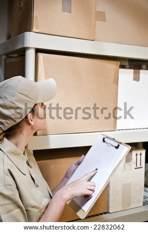 A young warehouse worker taking inventory - stock photo