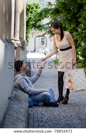A young, wealthy woman gives money to a beggar - stock photo