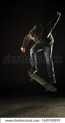 A young white Caucasian skateboarder doing an ollie jump at night. Lit with professional studio lighting on a black background.
