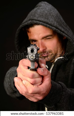 A young white, italian, male holds a semi automatic pistol during this dark photo shoot against black