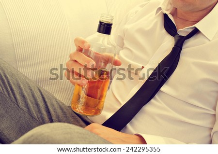 a young with his necktie loosened is drinking alcohol from a bottle - stock photo