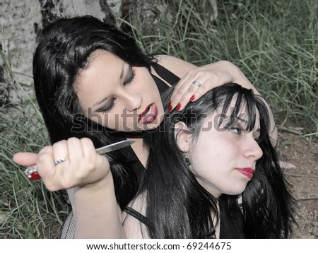 A young woman about to sacrifice another one in the forest with a razor