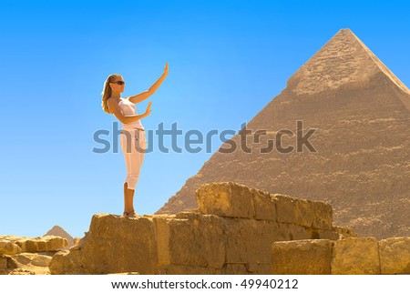 A young woman admires the Egyptian pyramids - stock photo