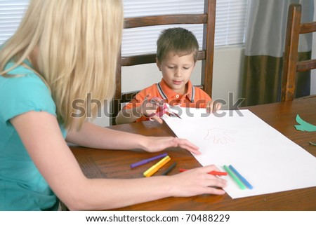 A young woman and a child cutting paper with scissors - stock photo