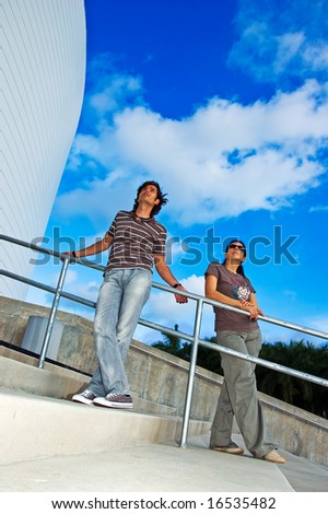 A young woman and a man (both asian-caucasian) looking upwards on a sunny day - stock photo