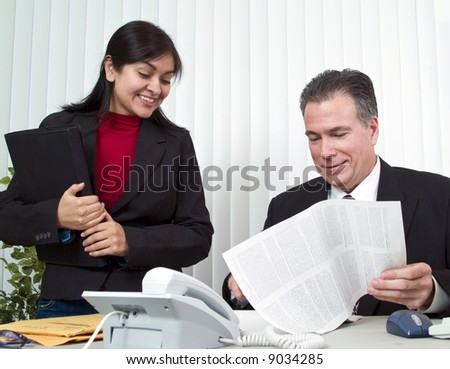 A young woman and a man looking over a document on legal size paper.