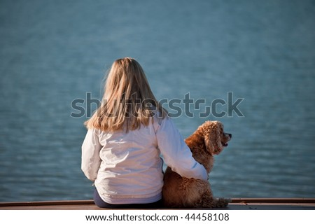 A young woman and her dog at the lake - stock photo