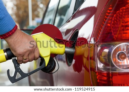 a young woman at a gas station gasoline tank. the cost of the car because of the gas prices are getting more expensive - stock photo