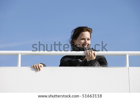 A young woman at a guardrail during a ship transfer - stock photo