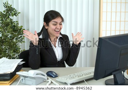 A young woman at her desk, thrilled or surprised by something on her computer monitor. - stock photo