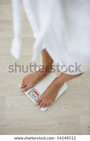 A young woman being weighed on a bathroom scale - stock photo
