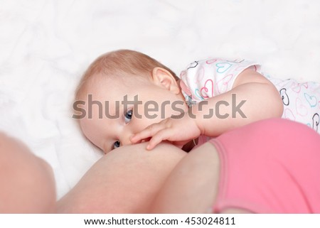 A young woman breast-feeding a baby lying on the bed