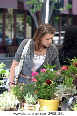 A young woman buying herbs for her garden - stock photo