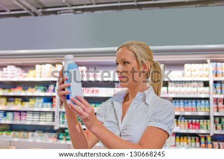 a young woman buys milk at the supermarket. stands in front of the refrigerated section.