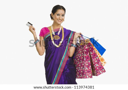 A young woman carrying shopping bags and a credit card