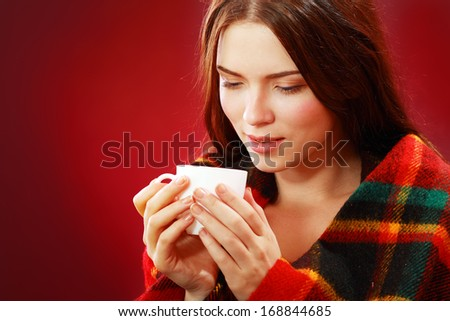 A young woman caught a cold covered with woolen plaid blanket - stock photo