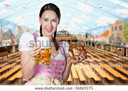 A young woman celebrating in a crowded Oktoberfest tent setting. - stock photo