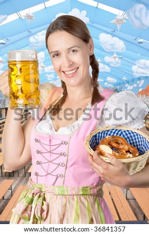 A young woman celebrating in an Oktoberfest tent setting with a mass of beer. - stock photo