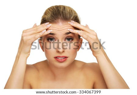 A young woman checking wrinkles on her forehead, closeup - stock photo