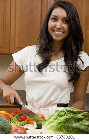 A young woman chopping vegetables for dinner - stock photo