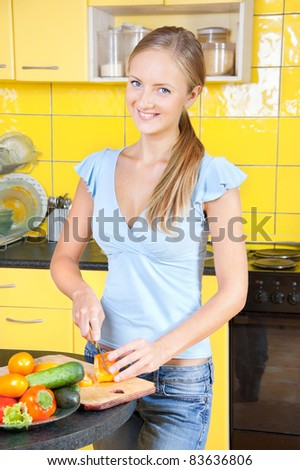 A young woman chops vegetable salad - stock photo