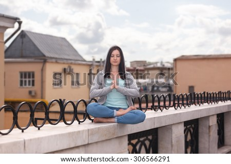 A young woman clad in hoodie in a yoga posture on the city parapet - stock photo