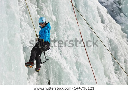 A young woman climbs a frozen waterfall in South Tyrol, Italy.