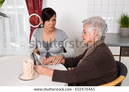 a young woman comforting a widow after death. grief counseling.