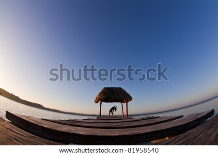 A young woman completes early morning exercise. Lake Peten. - stock photo