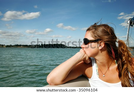 A young woman contemplating life on a beautiful lake in Montana. - stock photo