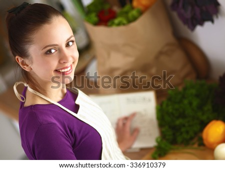 A young woman cooking in the kitchen. - stock photo