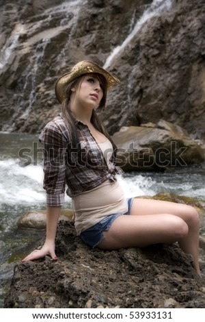 A young woman cowgirl sitting on a big rock by the river with waterfalls in the background. - stock photo