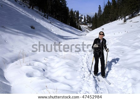A young woman cross country skiing in Yellowstone National Park - stock photo