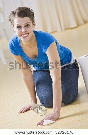 A young woman crouching down and using paper towels to clean up a spilled drink.  She is smiling and is facing the camera. Vertically framed shot. - stock photo