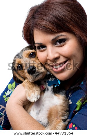 A young woman cuddling with a cute mixed breed puppy isolated on a white background. The dog is half beagle and half yorkie terrier. - stock photo