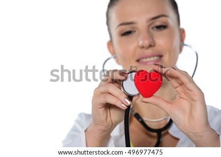 A young woman doctor with stethoscope examining red heart, isolated on white  background