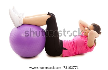 A young woman doing an abdominal crunch using a purple exercise ball