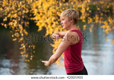 A young woman doing Tai Chi by a river - stock photo