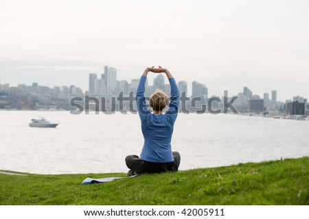 A young woman doing yoga on a hill top facing a city - stock photo