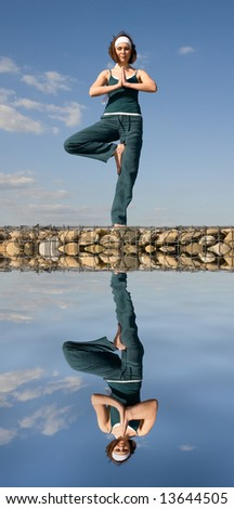 A young woman doing yoga on a stone above  water - stock photo