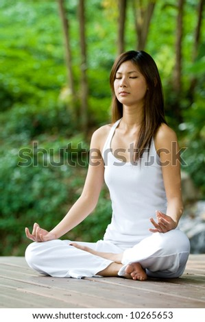 A young woman doing yoga outside in natural environment - stock photo