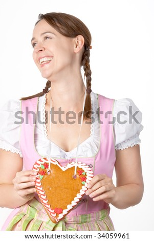 A young woman dressed in a traditional Bavarian Dirndl with a blank Herzl - on white - stock photo