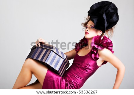 A young woman dressed in avant garde attire and holding a hat box. She is wearing a hat and has cosmetic artwork on her right temple. Horizontal shot. - stock photo