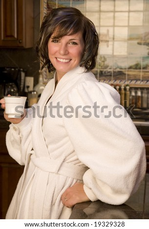 A young woman drinking coffee in her morning robe - stock photo