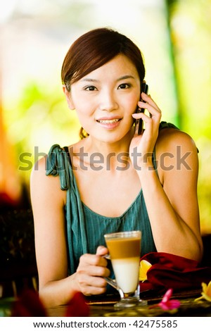A young woman drinking coffee while talking on the phone