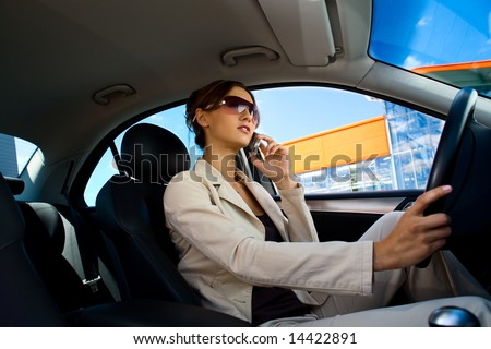 a young woman driving a car and phoning