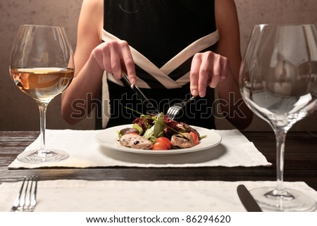 A young woman eating meat salad with stewed and fresh vegetables at an elegantly served table in a restaurant - stock photo