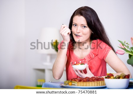 a young woman eating yogurt in the kitchen