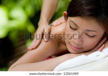 A young woman enjoying a massage outside